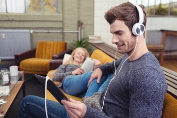 paar entspannt zu hause mit lesen und musik hören