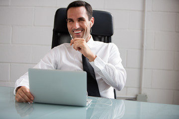 Businessman with laptop computer and earphones