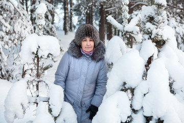 Happy mature woman in winter forest with snow covered branches