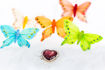Decorative heart and butterflies in white snow