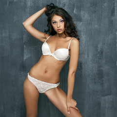 Sexy woman in white underwear on a dark wall
