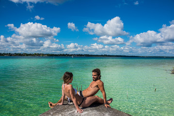 Beautiful couple in love looking at tranquil Bacalar lake.