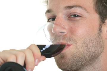 Casual young man holding glass of wine, smiling. Isolated on