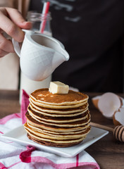 pile of Pancake with butter, pour honey, hand