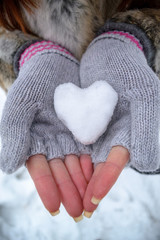 Heart of snow in mittens in the winter forest