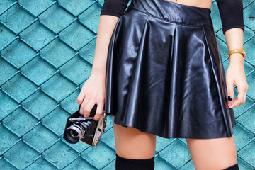 Girl with leather skirt and vintage camera
