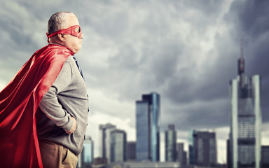 Senior superhero standing in front of a city