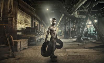 Attraktiver, muskulöser Mann mit Autoreifen