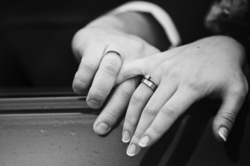 Close up snapshot of a husband lovingly holding his wife's hand.