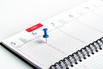 weekly agenda with spiral and blue pin