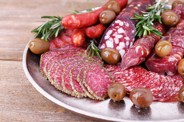 Fototapete - Sliced smoked sausages on metal tray on wooden table background