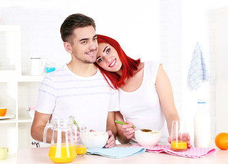 Happy couple has breakfast in kitchen