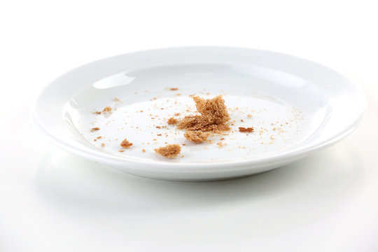 Bread crumbs on plate isolated on white