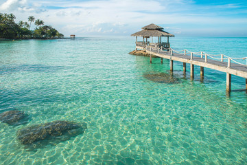Tropical hut and wooden bridge at holiday resort. Summer travel