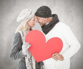 Wall Mural - Smiling couple in winter fashion posing with heart shape