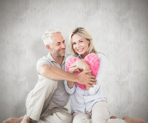 Composite image of happy couple sitting and holding heart pillow