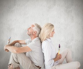 Composite image of happy couple sitting and holding paintbrushes