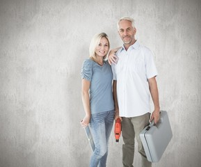Composite image of happy couple holding diy tools