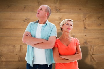 Composite image of thinking older couple with arms crossed