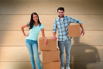 Composite image of attractive young couple with moving boxes