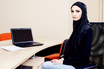 Muslim woman carrying the hijab while working on a laptop