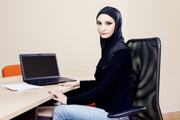 Muslim hijab wearer woman sitting at a desk with a computer