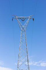 high voltage post, power transmission tower against blue sky