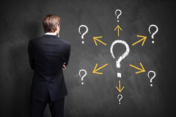 Geschäftsmann steht vor vielen Fragen