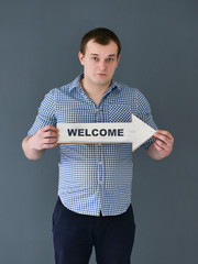 Young man holding welcome board banner and pointing something