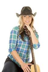 cowgirl with guitar in blue hand under chin