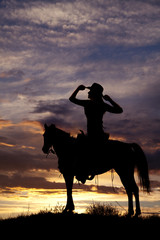 silhouette of a woman sitting on a saddle hands on hat