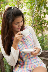 A shot of a beautiful asian woman drinking coffee in the garden
