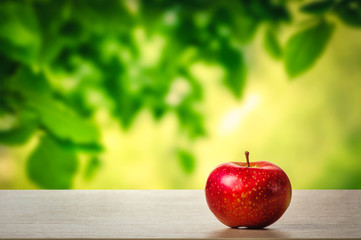 A red apple on the table in the garden