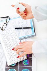 Doctor using a computer to prepare an on line prescription or wr