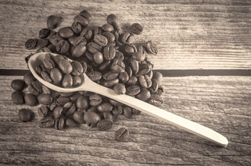 Black coffee and wooden spoon with coffee grains on wooden background