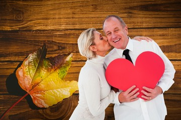 Wall Mural - Older affectionate couple holding red heart shape