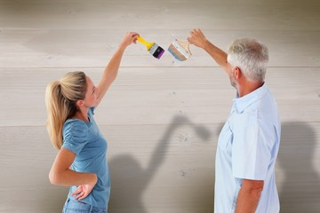Composite image of happy couple painting wall with paintbrushes