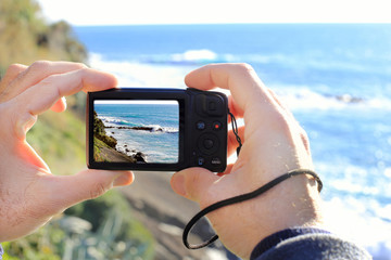 man hands taking picture of wild seascape