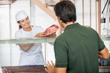 Female Butcher Selling Fresh Meat To Customer