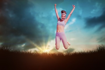 Composite image of sporty happy blonde jumping