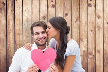 Wall Mural - Composite image of pretty brunette giving boyfriend a kiss