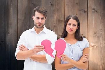 Upset couple holding two halves of broken heart