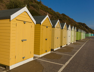 Gold and green beach huts in a row English seaside