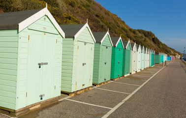 Green beach huts in a row traditional English structure