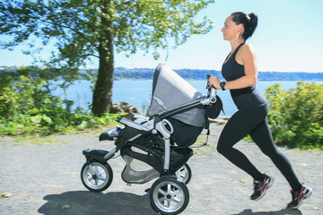 A Young mother jogging with a baby buggy