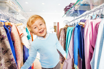 Happy blond small kid stands between hangers