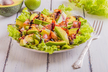 Avocado salad with fried bacon and pine nuts