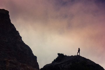 man on a cliff in mountains