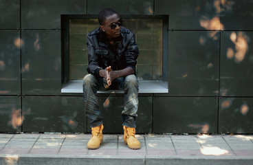 Wall Mural - Street fashion concept - stylish young african man in the city