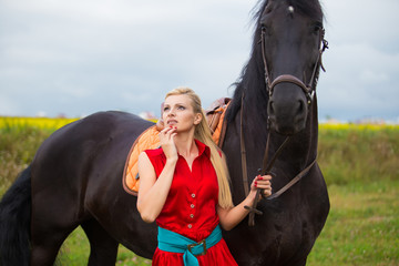 Fashionable blonde woman riding a horse in sunny day. Long hair.